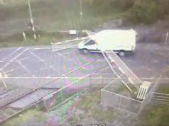 van smashes through railway barriers
